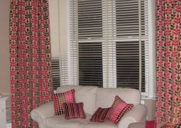 Curtains with pelmet board and scatter cushions to tie in and finish